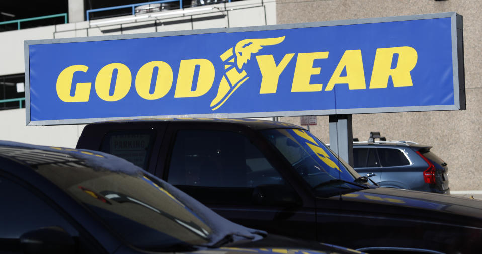In this Monday, Dec. 30, 2019, file photograph, the company sign hangs over vehicles waiting for repair outside a Goodyear Tire and Service store in downtown Denver. (AP Photo/David Zalubowski)