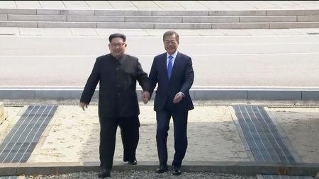 North Korean leader Kim Jong Un and South Korean President Moon Jae-in walk across the military demarcation line ahead of the inter-Korean summit at the truce village of Panmunjom, in this still frame taken from video, South Korea April 27, 2018. Host Broadcaster via REUTERS TV