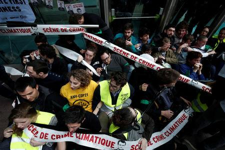 """Environmental activists block the entrance of the French bank Societe Generale headquarters during a """"civil disobedience action"""" to urge world leaders to act against climate change, in La Defense"""