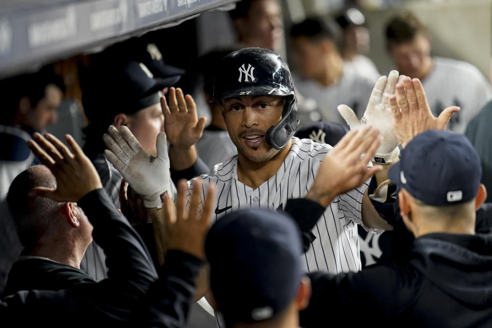 New York Yankees' Giancarlo Stanton celebrates in the dugout after hitting a solo home run off Cleveland Indians relief pitcher Jean Carlos Mejía during the eighth inning of a baseball game Friday, Sept. 17, 2021, in New York. (AP Photo/John Minchillo)