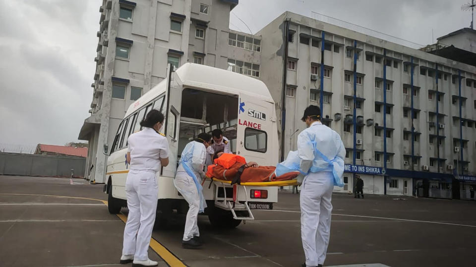 This photograph provided by Indian navy shows, one of the people rescued by the navy from the Arabian sea being brought for medical attention at naval air station INS Shikra in Mumbai, India, Tuesday, May 18, 2021. The Indian navy is working to rescue crew members from a sunken barge and a second cargo vessel that was adrift Tuesday off the coast of Mumbai after Cyclone Tauktae, struck the western coast. (Indian Navy via AP)