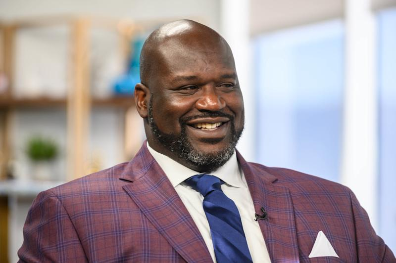 Shaquille O'Neal in a suit being interviewed.