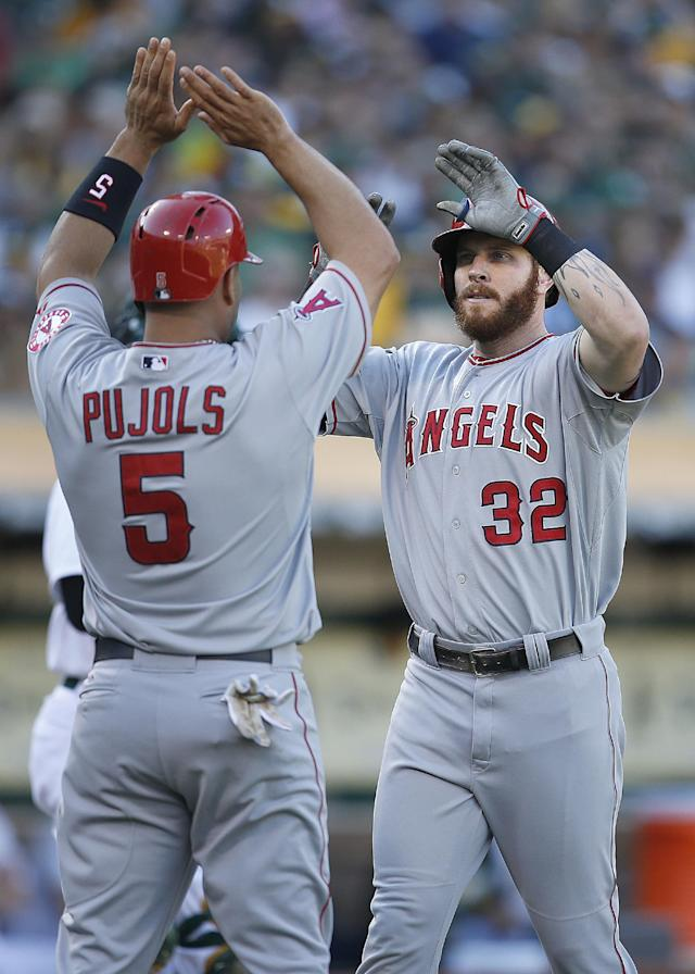 Los Angeles Angels' Josh Hamilton (32) is congratulated by Albert Pujols (5) after Hamilton hit a 2-run home run in the third inning against the Oakland Athletics of a baseball game Sunday, Aug. 24, 2014, in Oakland, Calif. (AP Photo/Tony Avelar)