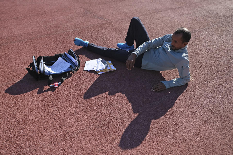 Birhanu Dare Kemal lies next to Bill Staab's bag, containing correspondence and checks for his team of runners, after a short workout at Van Cortlandt Park in the Bronx borough of New York, Tuesday, Nov. 26, 2019. Girma Bekele Gebre stunned the elite field at the New York City Marathon by finishing third as a nonelite entrant in November. It was a life-changing performance for the Ethiopian runner, and one made possible because of his involvement with the West Side Runners' Club. Team President Bill Staab has spent four decades helping immigrant runners acquire visas and gain entry to U.S. races, spending nearly $1 million of his own money to cover fees. Bekele Gebre is his greatest success, but not nearly the only runner he's helped. (AP Photo/Seth Wenig)
