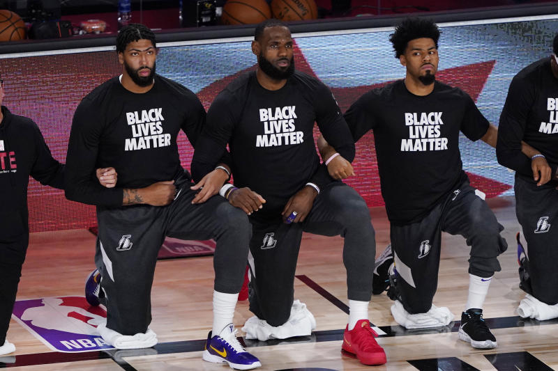 LAKE BUENA VISTA, FLORIDA - AUGUST 01: (L-R) Anthony Davis #3, LeBron James #23 and Quinn Cook #28 of the Los Angeles Lakers take a kneel before an NBA basketball game against the Toronto Raptors at The Arena in the ESPN Wide World Of Sports Complex on August 1, 2020 in Lake Buena Vista, Florida. NOTE TO USER: User expressly acknowledges and agrees that, by downloading and or using this photograph, User is consenting to the terms and conditions of the Getty Images License Agreement. (Photo by Ashley Landis - Pool/Getty Images)