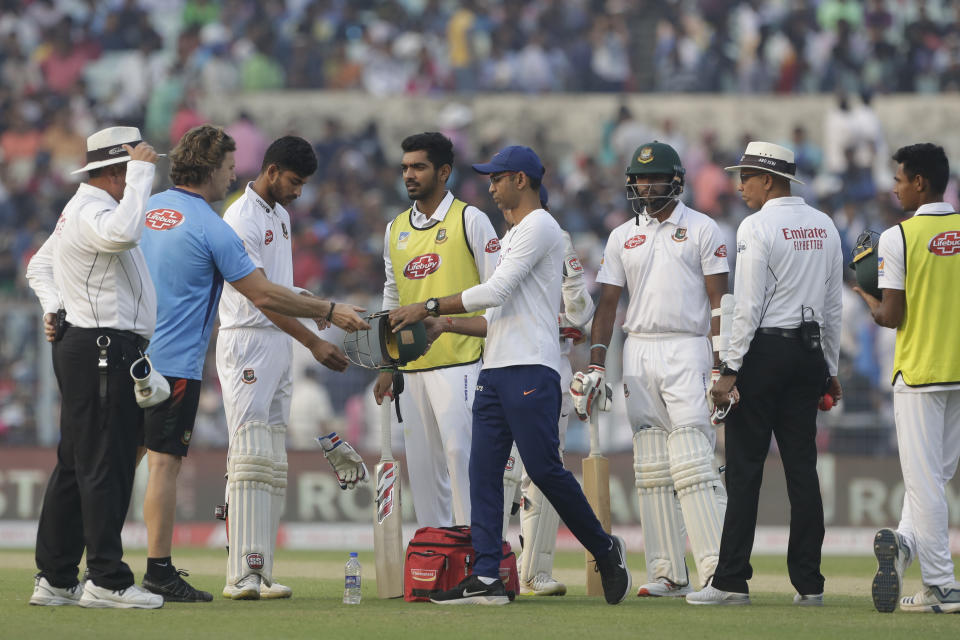Bangladesh's Nayeem Hasan, third left, stands as physiotherapists of India and Bangladesh look into the helmet after he was injured by a delivery by India's Mohammed Shami during the first day of the second test match between India and Bangladesh, in Kolkata, India, Friday, Nov. 22, 2019. (AP Photo/Bikas Das)