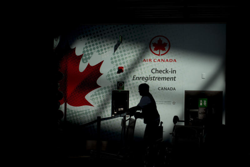 The silhouette of an Air Canada employee is seen near a check-in counter at Toronto Pearson International Airport in 2013.