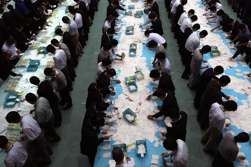 Electoral officials count ballots for the general election at the Himeji City Office in Himeji, Hyogo Prefecture, Japan, on Oct. 22, 2017.