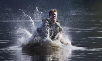Farrell Thomas, of Lake Forest, Ill., splashes into a lake as he successfully completes a jump in a water obstacle course, Friday, Aug. 7, 2020, in West Point, N.Y. The pandemic is not stopping summer training at West Point. Cadets had to wear masks this year for much of the training in a wooded area just beyond the main gates of the U.S. Military Academy. (AP Photo/Mark Lennihan)