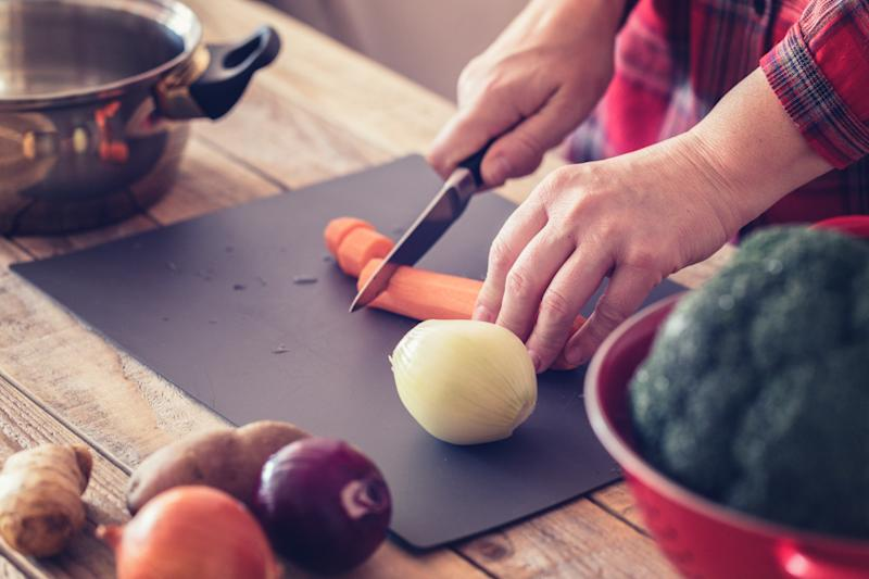Cooking at home - Vegetable soup preparing, female hand holding kitchen knife, chopping carrot and onions