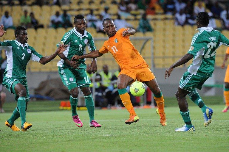 Didier Drogba (C) clashes with Kenneth Omeruo (R) in Rustenburg on February 3, 2012 in an Africa Cup of Nations game