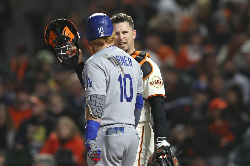 Los Angeles Dodgers' Justin Turner (10) talks with San Francisco Giants catcher Buster Posey during the fourth inning of Game 1 of a baseball National League Division Series Friday, Oct. 8, 2021, in San Francisco. (AP Photo/John Hefti)