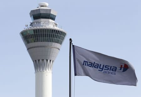 Malaysian Airlines flag flies in front of the traffic control tower at Kuala Lumpur International Airport in Sepang