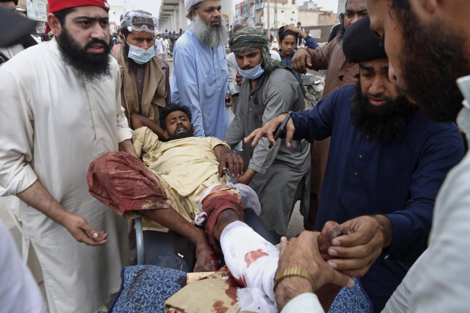 Supporters of Tehreek-e-Labiak Pakistan, a banned Islamist party, help their colleague who was injured during a clash police, in Lahore, Pakistan, Sunday, April 18, 2021. A crackdown by security forces on protesting supporters of the banned party left several people dead and many others, including police officers, injured, a police spokesman said Sunday. (AP Photo/K.M. Chaudary)