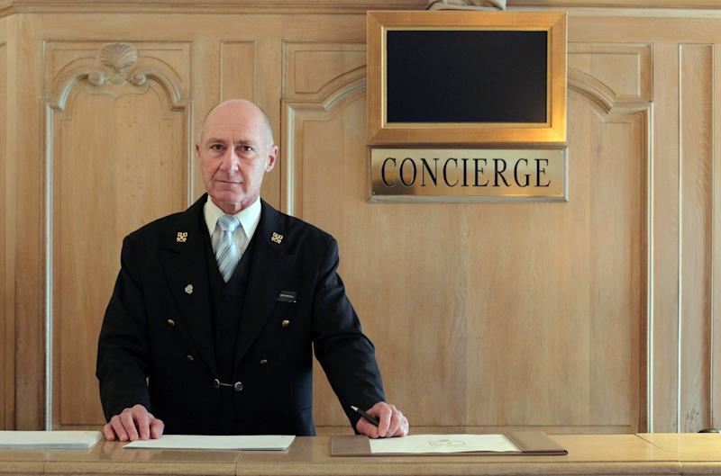 French Stephane Fanciulli, chief concierge of the Intercontinental Carlton Hotel, poses behind the reception desk of the hotel on January 4, 2013 in Cannes, southeastern France. AFP PHOTO / JEAN CHRISTOPHE MAGNENET (Photo credit should read JEAN CHRISTOPHE MAGNENET/AFP via Getty Images)