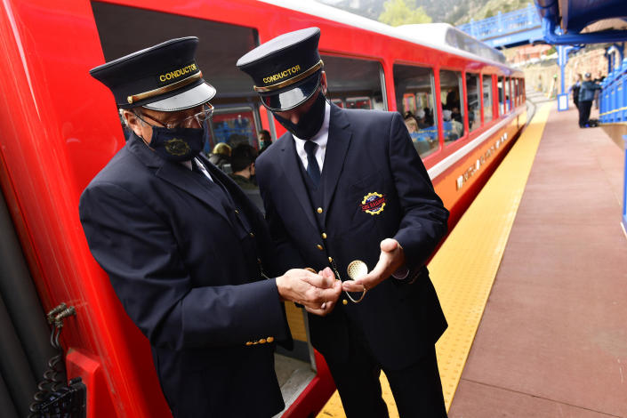 Conductors David Bolser, left, and Adam Clawson, right, check the time on their pocket watches as they helps get passengers aboard The Broadmoor Manitou and Pikes Peak Cog Railway train in May 2021. / Credit: Helen H. Richardson/MediaNews Group/The Denver Post via Getty Images