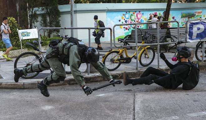 A riot police officer falls over in the process of trying to arrest a protester. Photo: Sam Tsang