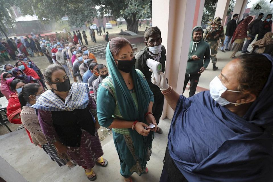 Jammu: People arriving at a polling station undergo thermal screening during the second phase of the District Development Council(DDC) elections at Meen Sarkar Sambha in Jammu