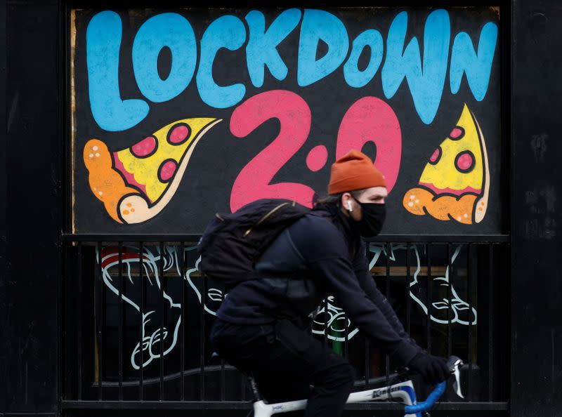 A man cycles past a mural on the boarded up window of a closed pizza restaurant in Manchester