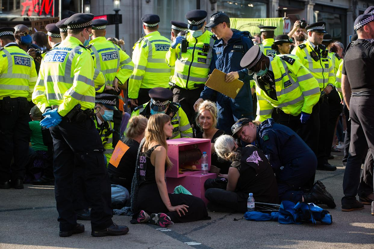 Metropolitan and other police officers prepare to remove and arrest Extinction Rebellion activists who had taken part in a pink roadblock of Oxford Circus by women and FINT-identifying environmental activists during the third day of Impossible Rebellion protests on 25th August 2021 in London, United Kingdom. Extinction Rebellion are calling on the UK government to cease all new fossil fuel investment with immediate effect. (photo by Mark Kerrison/In Pictures via Getty Images)