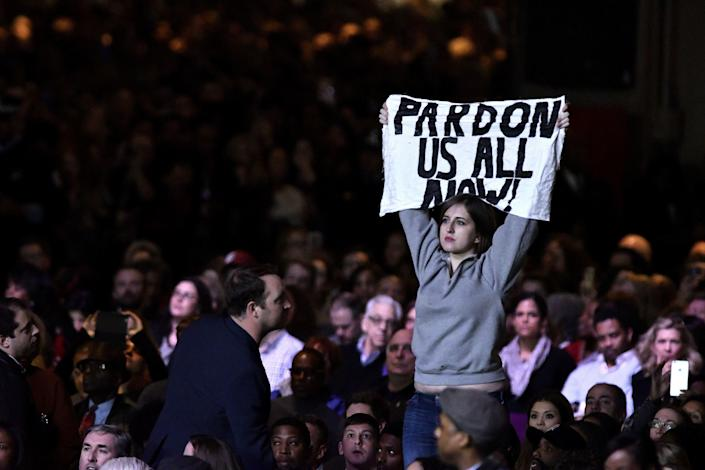 """A protester holds up a sign reading """"Pardon Us All Now!"""""""