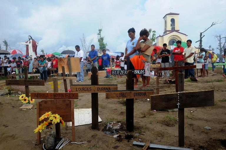 Relatives of the victims of Tyhpoon Haiyan attend a mass in front of the San Joaquin Church in Palo, Leyte, on December 8, 2013