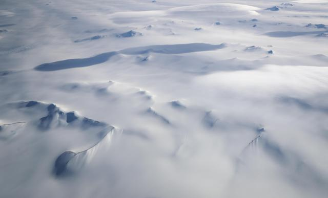 <p>Mountains peek through land ice as seen from NASA's Operation IceBridge research aircraft in the Antarctic Peninsula region on Nov. 4, 2017, above Antarctica. (Photo: Mario Tama/Getty Images) </p>