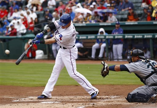 Texas Rangers' Josh Hamilton (32) hits a double in front of Seattle Mariners catcher Miguel Olivo (30) in the first inning of a baseball game Sunday, Sept. 16, 2012, in Arlington, Texas. (AP Photo/Jim Cowsert)