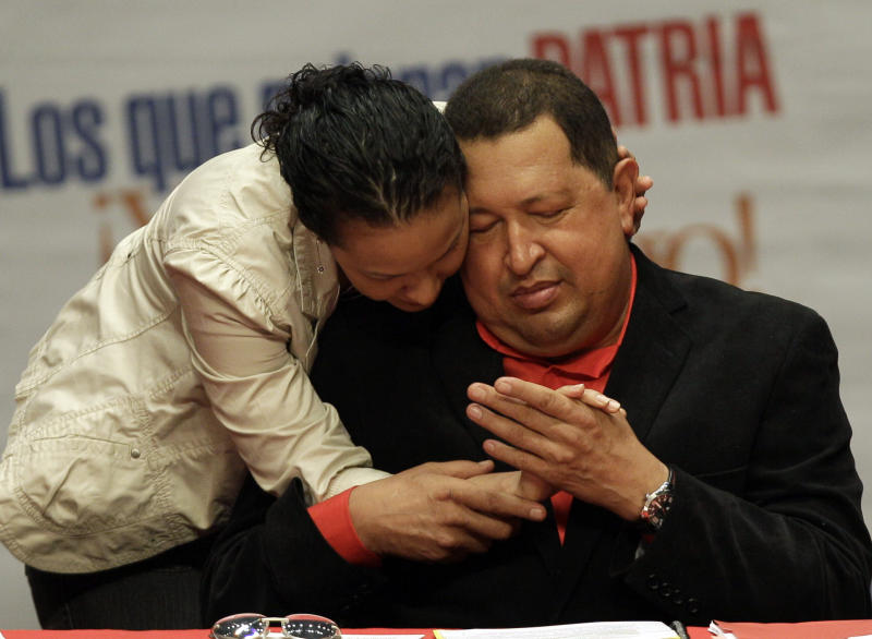 Venezuela's President Hugo Chavez, right, is greeted by his daughter Rosa as he attends a concert in his honor atTeresa Carreno theater  in Caracas, Venezuela, Thursday, Feb. 23, 2012. Chavez is headed to Cuba for surgery to remove a potentially cancerous tumor while the nation's congress on Thursday unanimously approved permission for Chavez to leave, a formality required by the nation's constitution. (AP Photo/Fernando Llano)