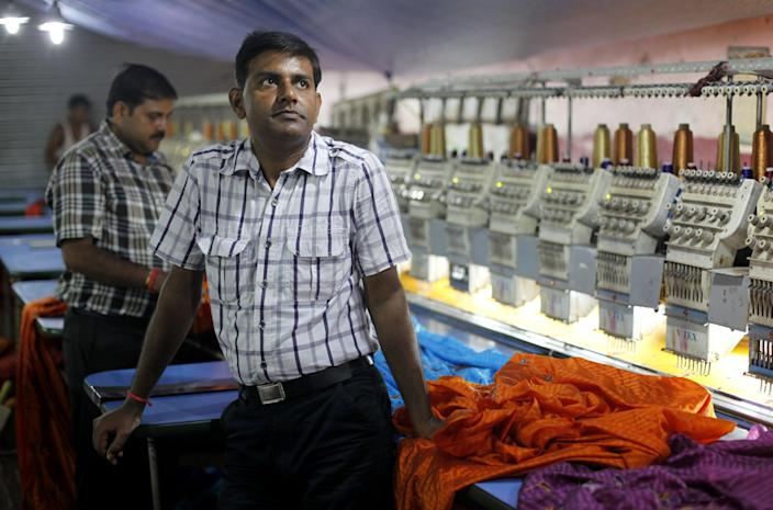In this Monday, Sept. 2, 2013 photo, Indian Pradeep Kumar Yadav, 42, stands inside his embroidery factory in Varanasi, India. Despite nearly two decades of rapid economic growth, most Indians are risk averse and do not own stocks or equities. (AP Photo/ Rajesh Kumar Singh)