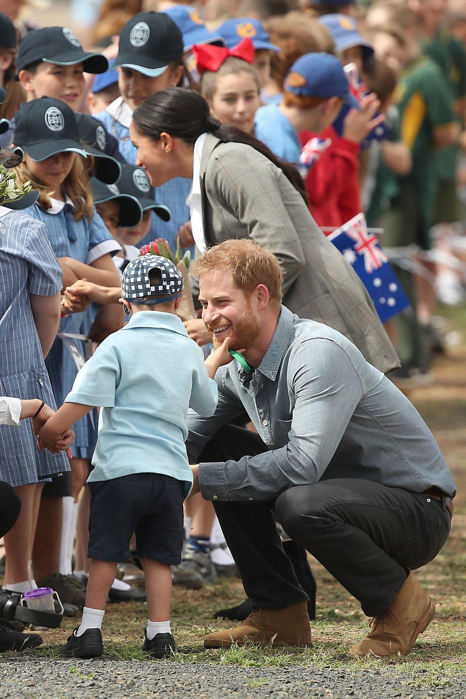 """<p>When Harry and Meghan visited Dubbo, little Luke stepped forwards to give Harry a hug and stroke his beard. His teacher <a href=""""https://www.goodhousekeeping.com/uk/lifestyle/a23860779/prince-harry-luke-jenkins-hug-dubbo-new-south-wales/"""" rel=""""nofollow noopener"""" target=""""_blank"""" data-ylk=""""slk:reportedly said that as Luke's favourite person is Santa Claus"""" class=""""link rapid-noclick-resp"""">reportedly said that as Luke's favourite person is Santa Claus</a>, who has a beard, he rubbed Harry's </p>"""
