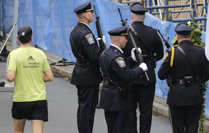 A runner passes as Boston Police honors change their post outside the Marathon Sports store, the site of the first of two bombs that exploded near the finish line of the 2013 Boston Marathon, Tuesday, April 15, 2014 in Boston. Three were killed and more than 260 injured in last year's explosions near the finish line of the race. (AP Photo/Charles Krupa)