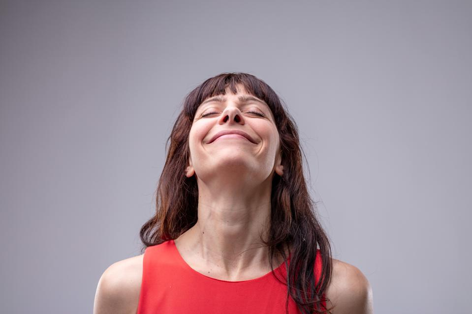 Happy woman with her head thrown back and a beaming wide smile of pleasure with closed eyes over grey with copy space