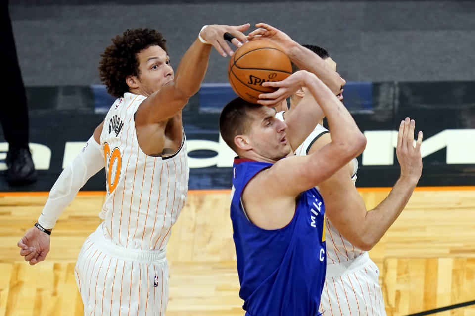 Orlando Magic forward Aaron Gordon, left, comes from behind to block as shot by Denver Nuggets center Nikola Jokic during the first half of an NBA basketball game, Tuesday, March 23, 2021, in Orlando, Fla. (AP Photo/John Raoux)
