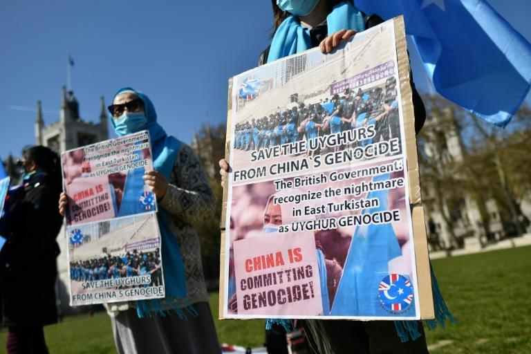 Members of the Uyghur community hold placards on April 22, 2021 as they demonstrate to call on the British parliament to vote to recognize treatment of the minority by China as genoicde