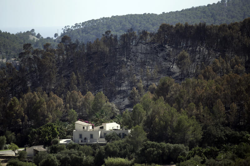 A house is surrounded by burnt trees after a fire, near the village of Andratx on the Spanish Balearic island of Mallorca, Spain, Sunday, July 28, 2013. The regional government of Spain's Balearic Islands says a wildfire is raging out of control in Mallorca, the popular Mediterranean luxury tourist destination. A statement says some 700 residents had to be evacuated early Sunday morning from the village of Estallencs as fires fanned by winds spread eastward along wooded hills. (AP Photo/Manu Mielniezuk)