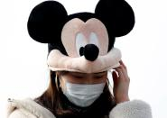 A visitor wearing protective face mask and Mickey Mouse costume, following an outbreak of the coronavirus, is seen outside Tokyo Disneyland in Urayasu