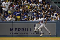 A ball boy removes an inflatable trash can from the field during the seventh inning of a baseball game between the Los Angeles Dodgers and the Houston Astros on Tuesday, Aug. 3, 2021, in Los Angeles. (AP Photo/Marcio Jose Sanchez)