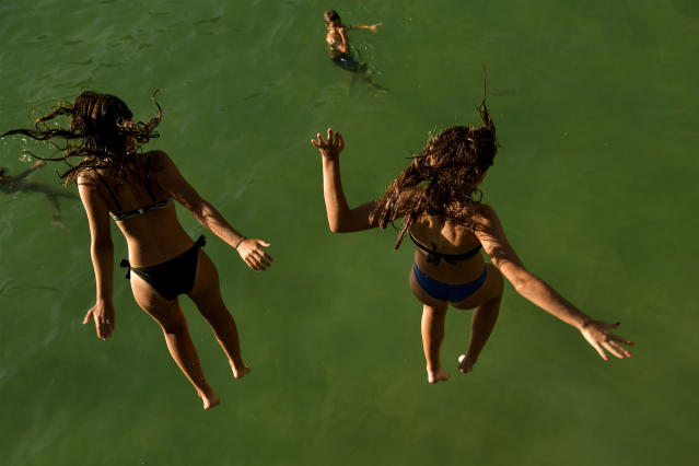<p>Two women jump from a platform over the water at La Concha beach during a hot summer day in the basque city of San Sebastian, northern Spain, Friday, Aug. 3, 2018. (Photo: Alvaro Barrientos/AP) </p>