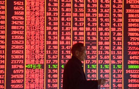 A man is seen in front of an electronic board showing stock information on the first day of trading in the Year of the Pig, following the Chinese Lunar New Year holiday, at a brokerage house in Hangzhou, Zhejiang province, China February 11, 2019. REUTERS/Stringer