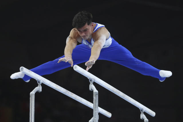 Artur Dalaloyan of Russia performs on the parellel bars in the men's team final at the Gymnastics World Championships in Stuttgart, Germany, Wednesday, Oct. 9, 2019. (AP Photo/Matthias Schrader)
