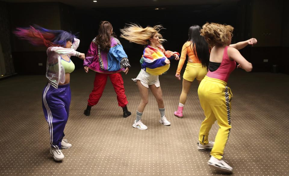 Catherine Gallano, dancer and lead choreographer, center, dances with her group during their livestream performance on social media for followers who send them money, in Dubai, United Arab Emirates, Thursday, Nov. 5, 2020. As the coronavirus pandemic mutes Dubai's live-music scene, the Filipino show bands that long have animated the city's storied nightlife are being disproportionately squeezed. Many are out of work and out of money, struggling to survive in overcrowded dormitories at the mercy of employers (AP Photo/Kamran Jebreili)