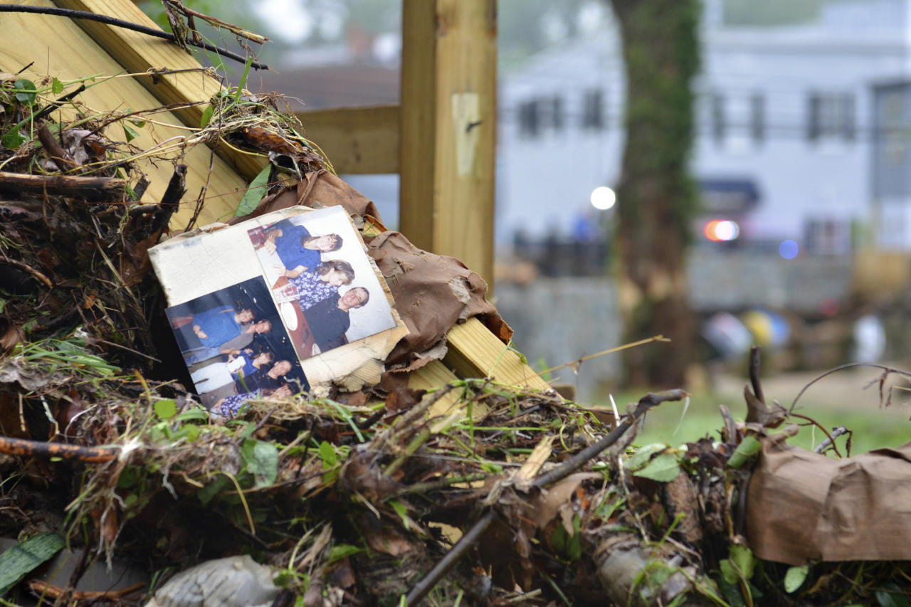 <p>Family photos rest among debris after flash flooding in Ellicott City, Md., Monday, May 28, 2018. Sunday's destructive flooding left the former mill town heartbroken as it had bounded back from another destructive storm less than two years ago. (Photo: David McFadden/AP) </p>