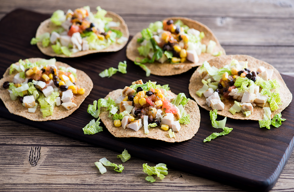 """<p>In English, tostada simply means toasted. Pile your toppings high with grilled chicken, healthy veggies and your favorite salsa. </p> <p><strong><a href=""""https://www.thedailymeal.com/recipes/chicken-salad-tostadas-recipe-0?referrer=yahoo&category=beauty_food&include_utm=1&utm_medium=referral&utm_source=yahoo&utm_campaign=feed"""" rel=""""nofollow noopener"""" target=""""_blank"""" data-ylk=""""slk:For the Chicken Salad Tostadas recipe, click here."""" class=""""link rapid-noclick-resp"""">For the Chicken Salad Tostadas recipe, click here.</a></strong></p>"""