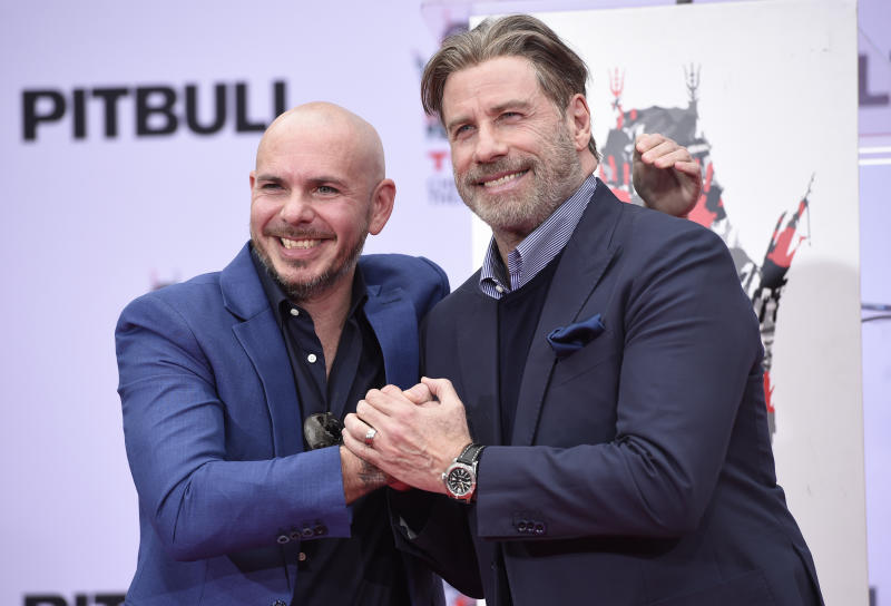 Actor John Travolta, left, and rapper Pitbull pose during a hand and footprint ceremony in Pitbull's honor at the TCL Chinese Theatre on Friday, Dec. 14, 2018, in Los Angeles. (Photo by Chris Pizzello/Invision/AP)