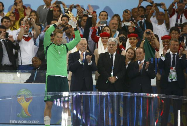 Germany's goalkeeper Manuel Neuer (L) holds the Golden Glove trophy after winning their 2014 World Cup final against Argentina at the Maracana stadium in Rio de Janeiro July 13, 2014. REUTERS/Kai Pfaffenbach (BRAZIL - Tags: SOCCER SPORT WORLD CUP)