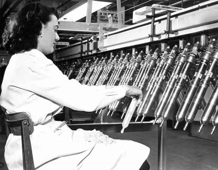A woman in white tests condoms on an automated production line.