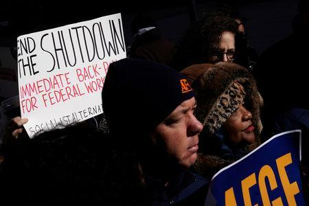 FILE PHOTO: Protestors hold signs during a rally outside a closed federal building in the Manhattan borough of New York City, New York, U.S., January 15, 2019. REUTERS/Carlo Allegri/File Photo