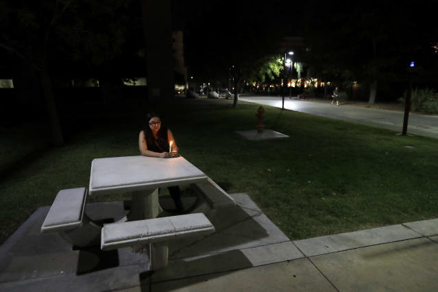 <p>University of Nevada Las Vegas student Johanna Munoz sits at a table with a candle during a vigil Monday, Oct. 2, 2017, in Las Vegas. A gunman on the 32nd floor of the Mandalay Bay casino hotel rained automatic weapons fire down on the crowd of over 22,000 at an outdoor country music festival Sunday. (Photo: Gregory Bull/AP) </p>