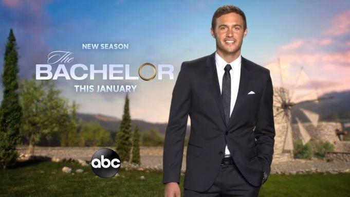 """Peter Weber stands in a promo in front of a windmill with the words """"New Season The Bachelor This January"""""""